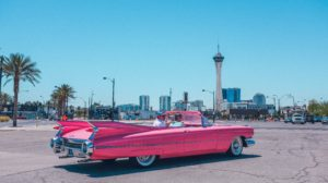 A pink old-timer car with Las Vegas in the background.