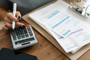 person calculating to organize your moving budget properly