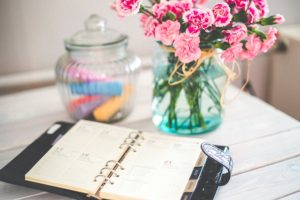 A planner notebook next to a vase with flowers.