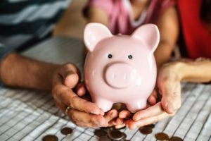 hands holding a money bank - ways to organize your moving budget properly