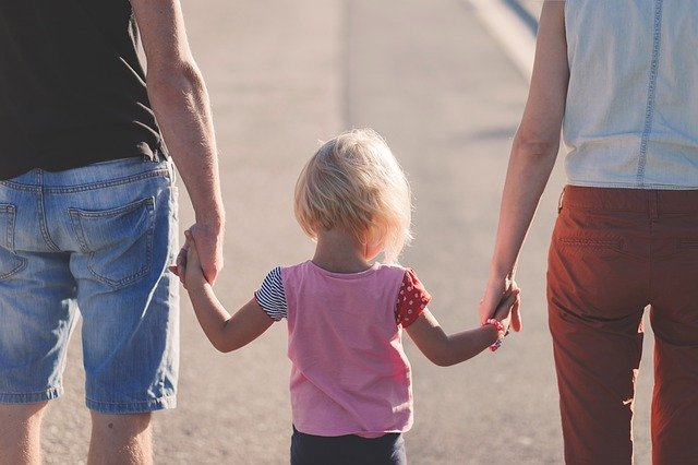 A child standing between its parents.