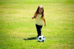 A girl playing football after her parents decided that moving to Las Vegas with children is a good decision.