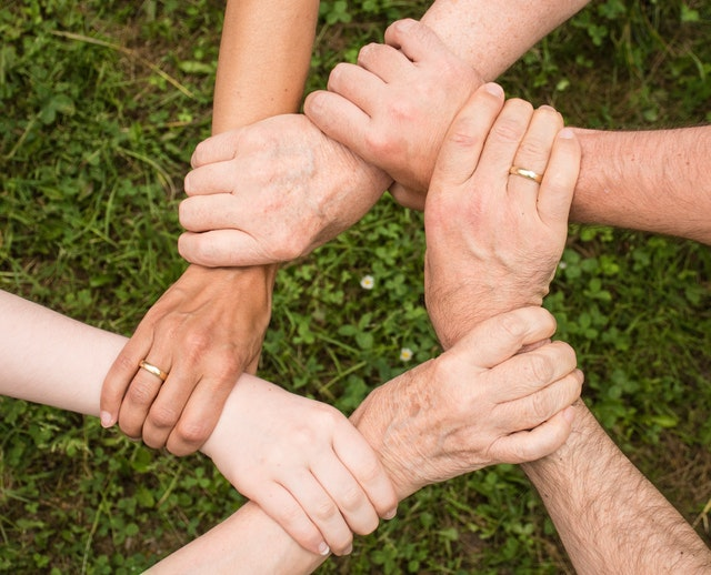 There are six hands of different people, holding each other, and making a circle.