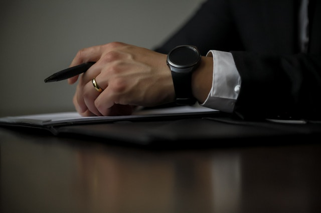 There is hand of a man, holding a pen, there is a black watch on the hand, and a ring.