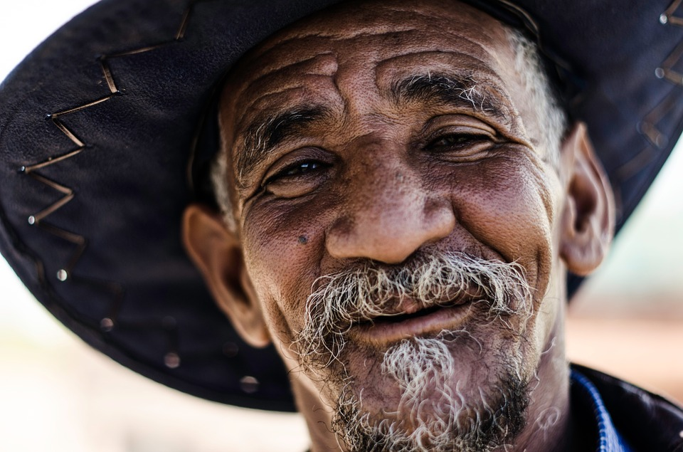 An older man with gray beard smiling while wearing a big hat.
