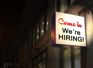 a neon 'we're hiring' sign