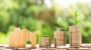 A house figurine and coins - downsizing your home.