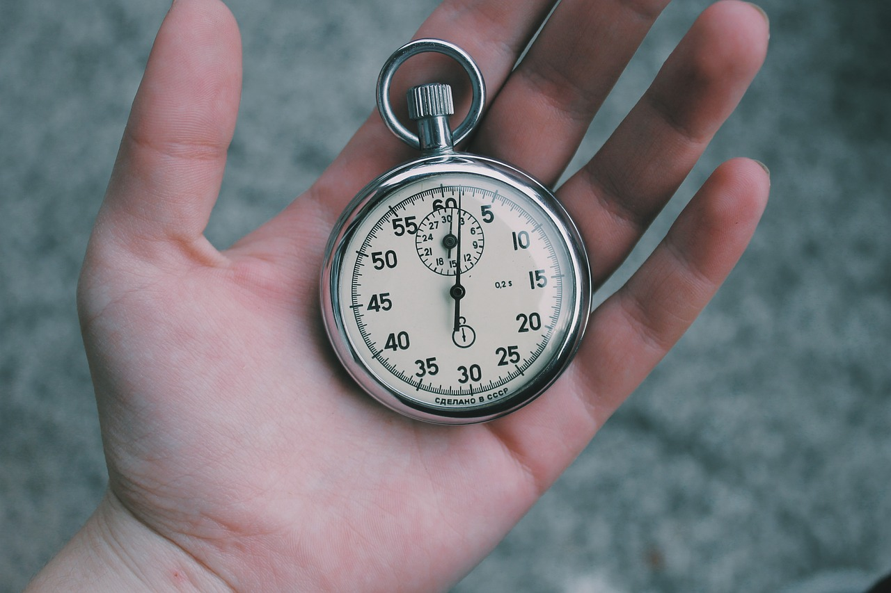 A person holding a stopwatch in the hand.