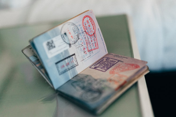A passport wide open with many stamps in it.
