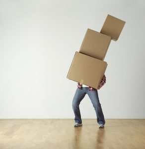 A man carrying a pile of cardboard boxes.