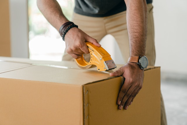 A man tapping up a cardboard box
