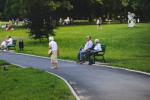 There are some senior people sitting and walking in a park in Massachusetts.