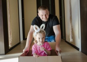 father and daughter playing with a moving box