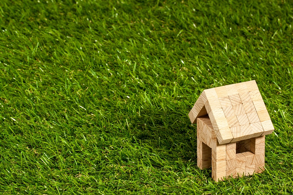 A small wooden model house on the green grass.
