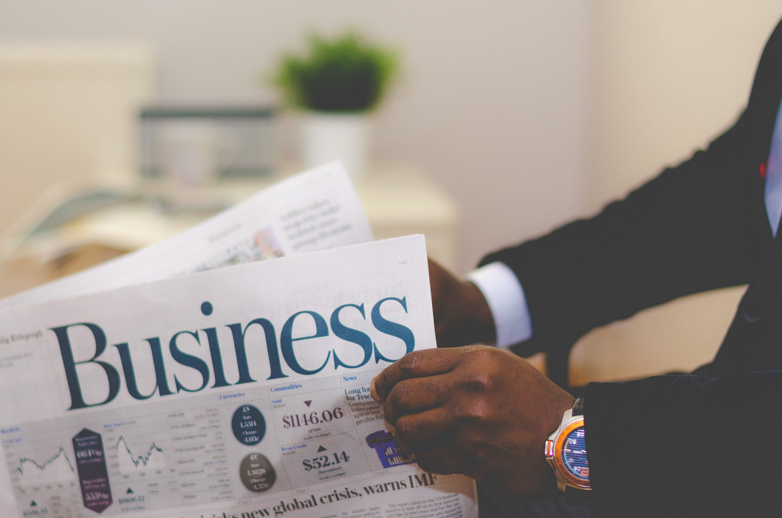 A man in a suit reading the Business magazine.