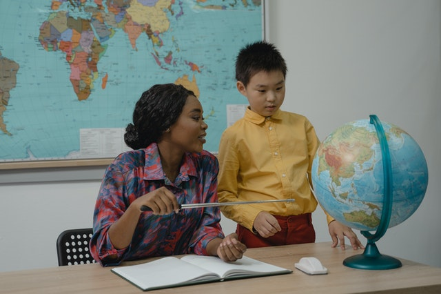 a female teach and a boy looking at a globe, read about 3 insightful tips for moving household items internationally
