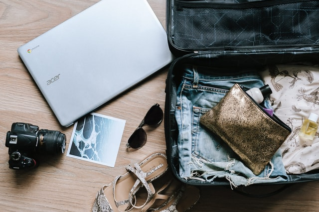 A laptop and a camera beside a suitcase
